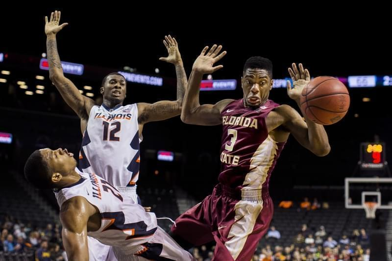 Three college basketball players fighting for a rebound.