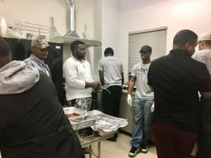 The Men of Impact kitchen crew includes Olivier Jacques (in John Deere hat), Uyi Idemudia (in white hoodie), and Dwayne Mitchell (in the Nike cap).