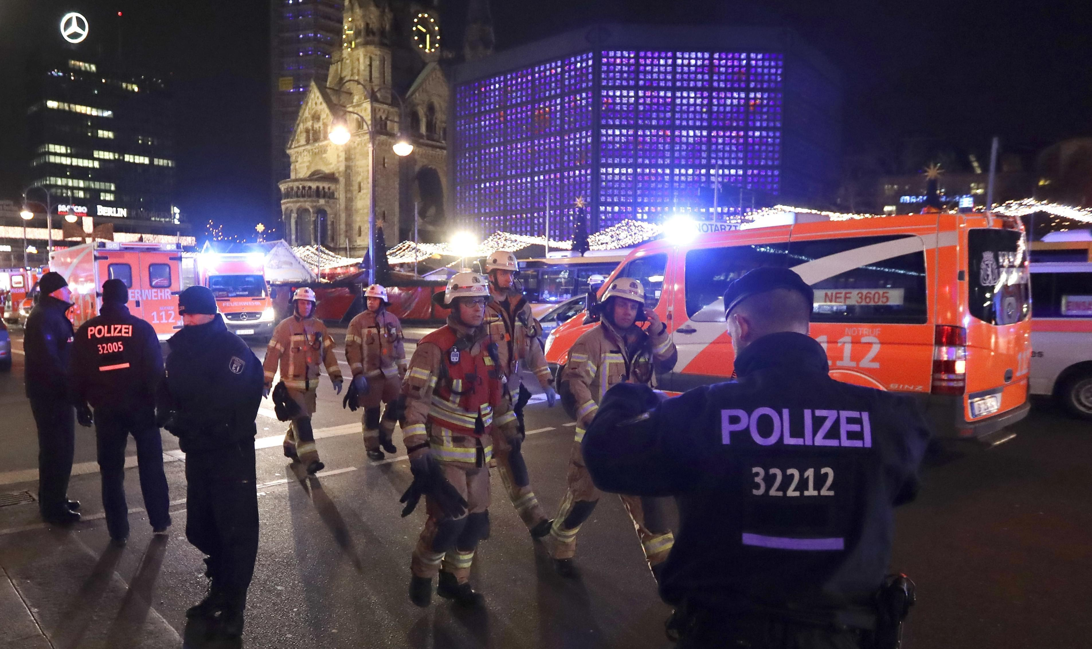 Firefighters walk past ambulances after a truck ran into a crowded Christmas market and killed several people in Berlin, Germany, Monday, Dec. 19, 2016.