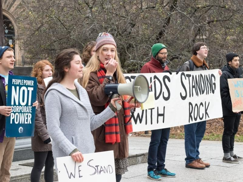 Seven college students, dressed for cold, stand in a line at a rally. One speaks into a megaphone and others hold signs.