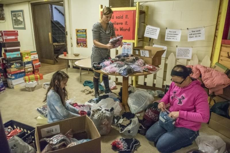 From left: Elana Whitsitt, Oksana Whitsitt and Brooke Riddell organize gifts as volunteers gathered to wrap gifts for the women and children of Courage Connection at Trinity Lutheran Church, Urbana, Il on December 15, 2016.