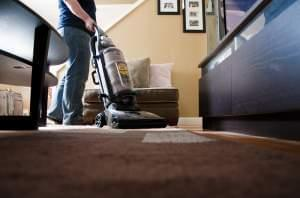 person vacuuming the floor