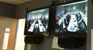 Video monitors show the Illinois Education Funding Reform Commission meets via speakerphone linking conference rooms in Springfield and Chicago.