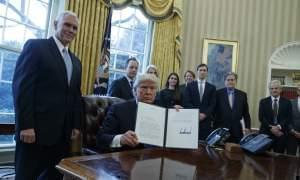 resident Donald Trump, accompanied by Vice President Mike Pence and staff, shows his signature on an executive order on the Keystone XL pipeline, Tuesday, Jan. 24, 2017, in the Oval Office of the White House in Washington.