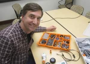 Joe Muskin with the University of Illinois College of Engineering looks up from an array of Lego Mindstorms components.