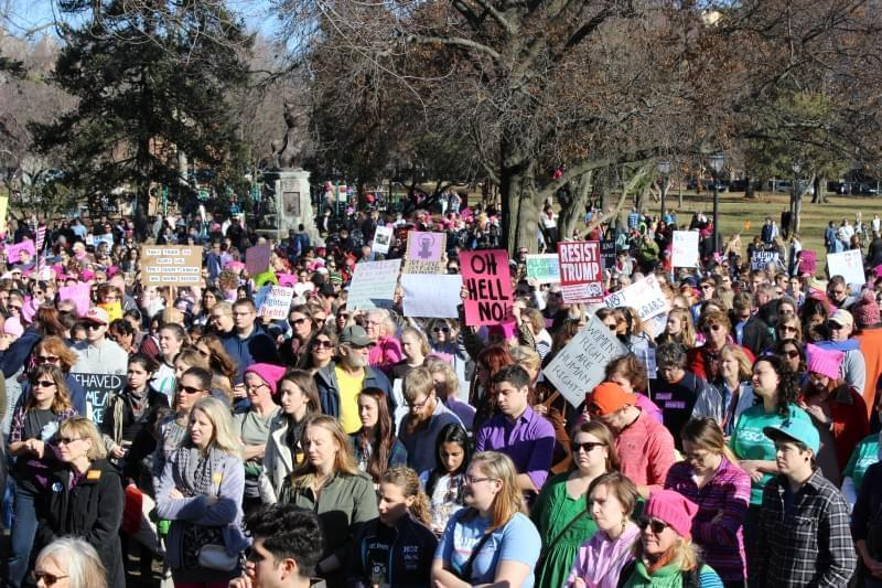 A crowd listens to guest speakers at the Jan. 21 women's march in Champaign's Westside Park.