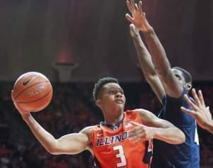 Illinois' guard Te'Jon Lucas (3) looks to pass under the basket as Penn State's forward Mike Watkins (24) defends during an NCAA college basketball game in Champaign.