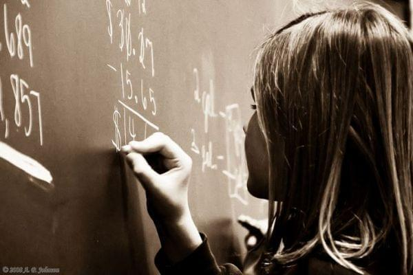 Young girl completing a math problem on a chalkboard