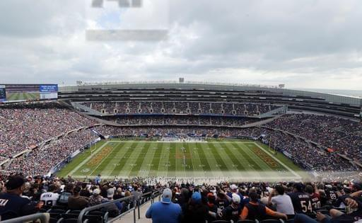 In this Oct. 2, 2016 file photo, fans watch an NFL football game between the Chicago Bears and the Detroit Lions, at Soldier Field in Chicago. The Chicago Bears and the NFL Players Association are at odds over a worker compensation benefit bill in th