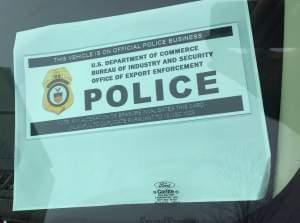 An official parking placard visible inside the windshield of a car parked in front of Caterpillar headquarters on Adams Street in downtown Peoria today