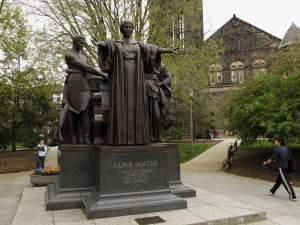 In this April 28, 2014 photo, students walk past the Alma Mater statue, a landmark on the University of Illinois campus in Urbana, Ill.