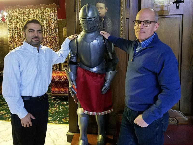 Developer Dionis Rodriguez and project manager Bill Walsh pose with a suit of armor in the Urbana Landmark Hotel