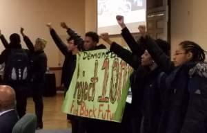 Members of the Black United Front unfurl a banner at Wednesday's University of Illinois trustees meeting.
