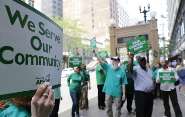 In this June 9, 2015 photo, members of the American Federation of State, County and Municipal Employees protest outside the in Chicago.
