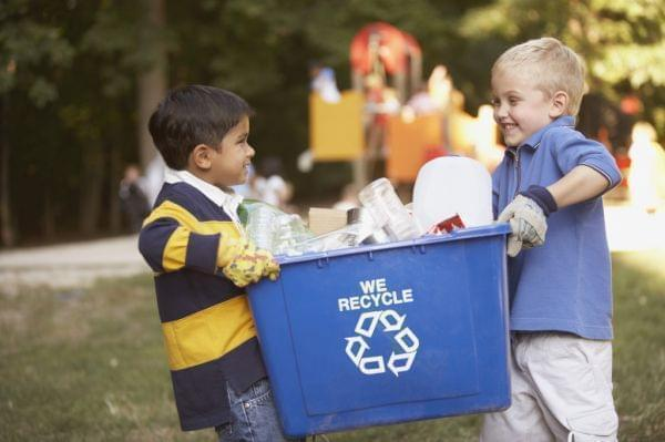 2 small children carrying  a recycling container