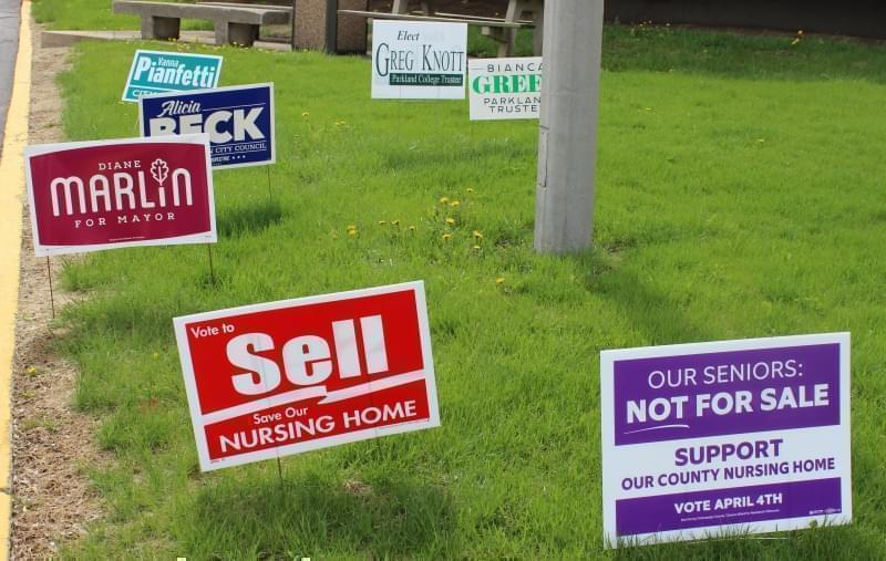 Campaign signs cover the lawn outside the Brookens Administrative Center in Urbana.
