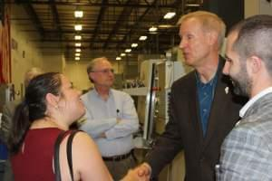 Rauner visits with supporters and employee at HL Precision Manufacturing in Champaign Wednesday.