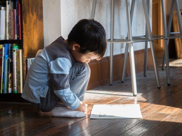 Small boy reading book on floor.