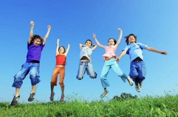 5 kids jumping in air outside
