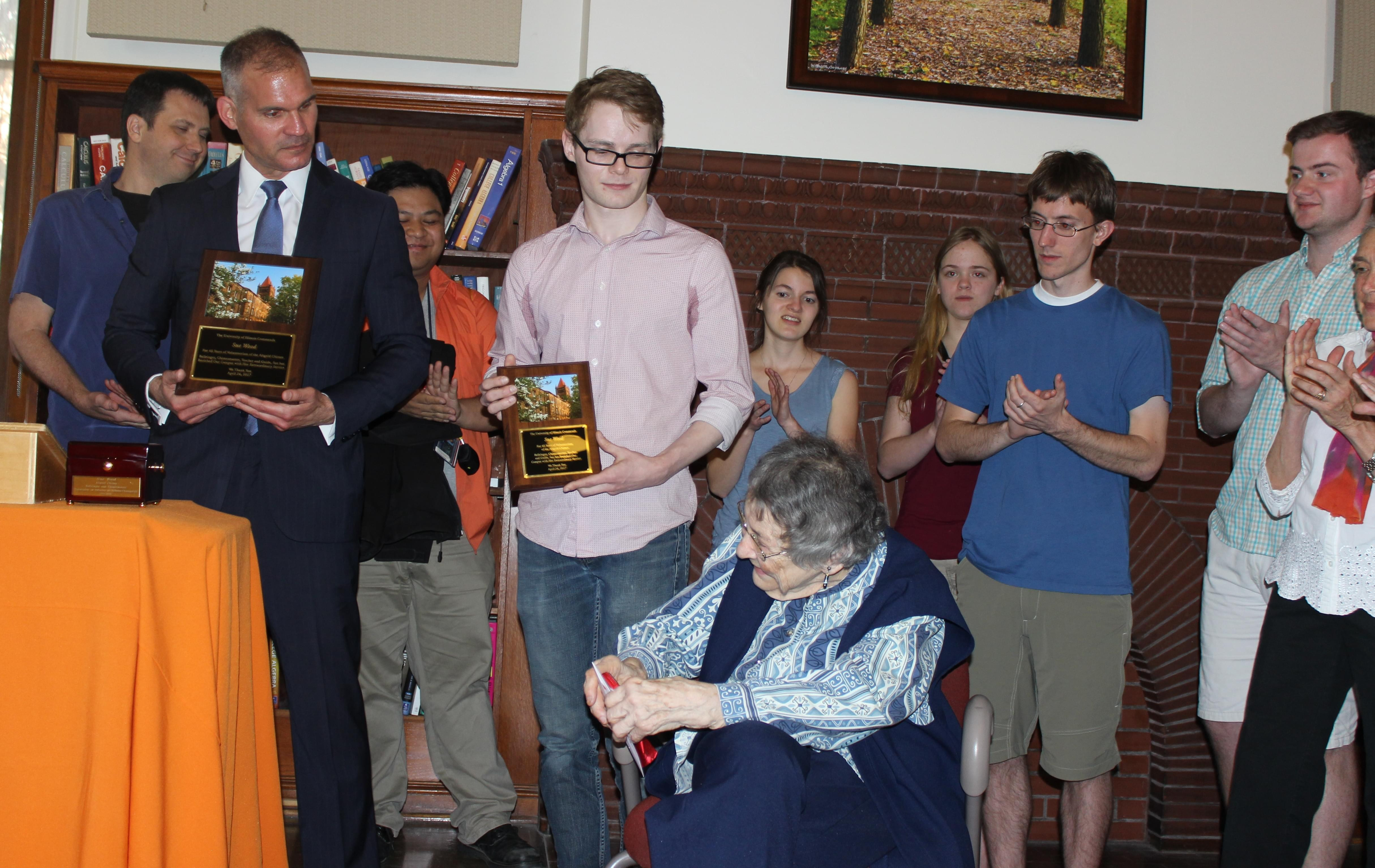 Sue Wood, center, is honored by volunteer chimes players and U of I Associate Provost Matthew Tomaszewski.