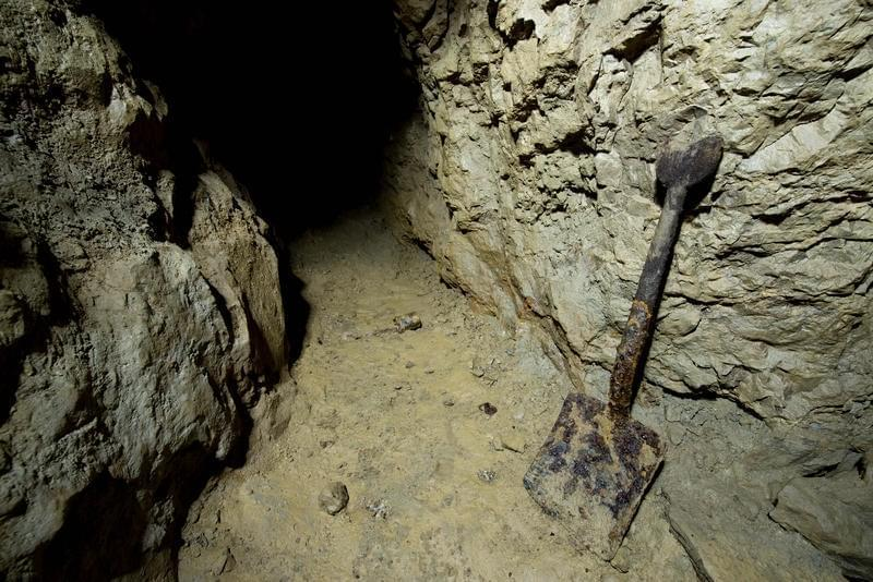 A shovel at the entrance to a cave.