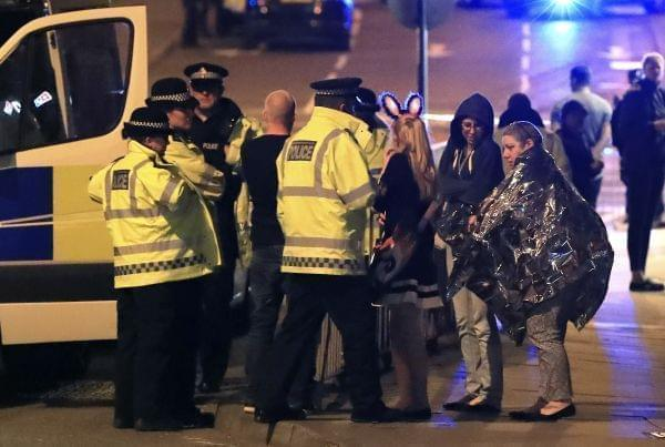 Emergency services personnel speak to people outside Manchester Arena after reports of an explosion at the venue during an Ariana Grande concert in Manchester, England,