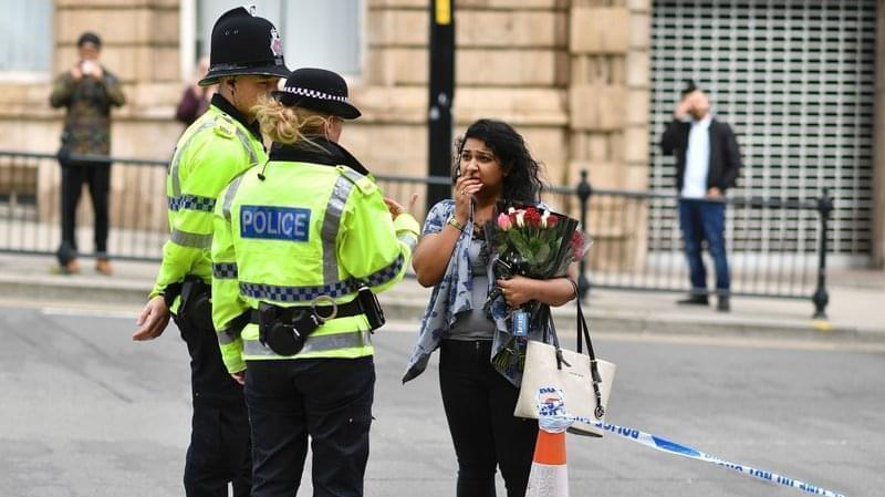 A woman speaks with police officers after bringing flowers close to the area where a bombing struck outside the Manchester Arena Monday night.