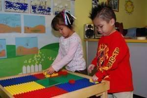 Preschool boy and girl playing at a Lego table in classroom