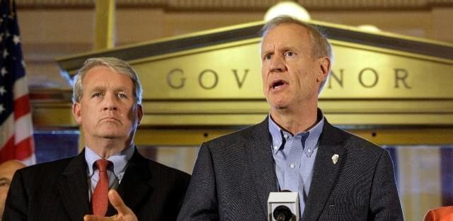 Illinois Gov. Bruce Rauner speaks to reporters in front of his office at the Illinois State Capitol on June 30, 2016, in Springfield. Looking on is Illinois House Minority Leader Jim Durkin.