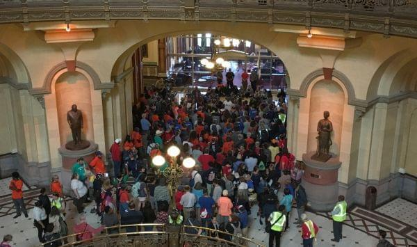 Protestors gathered outside the offices of Gov. Bruce Rauner Tuesday at the Illinois State Capitol.