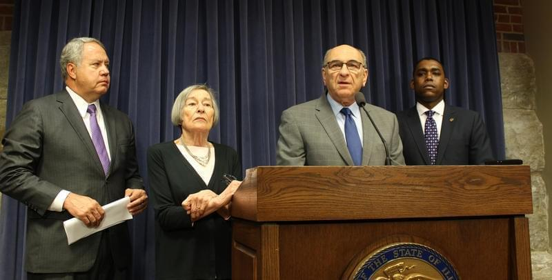 State Rep. Lou Lang, at podium, and other members of the Illinois House Democratic leadership team.