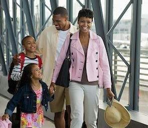 mom, Dad, and two children walking through the airport