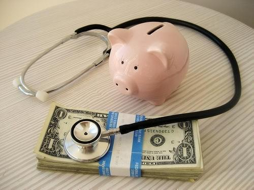 A piggy bank with a stethoscope and money.