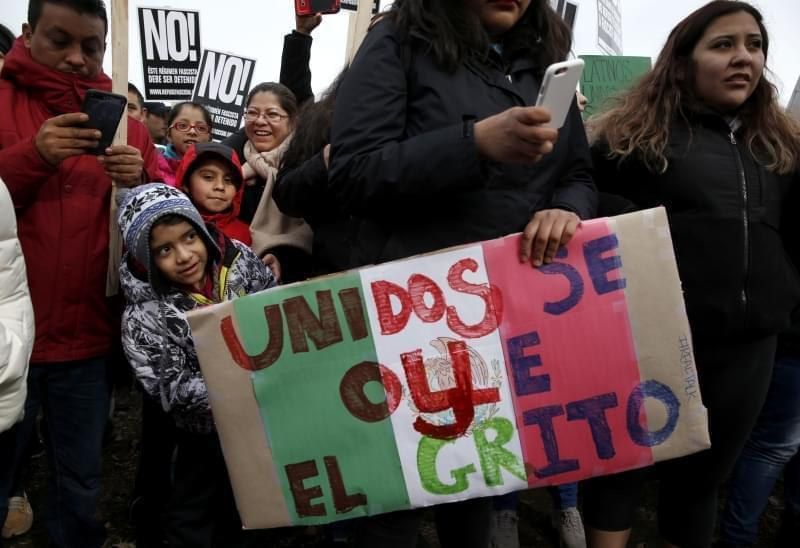 Protestors participate in a march holding signs aimed at President Donald Trump's efforts to crack down on immigration laws in Chicago.