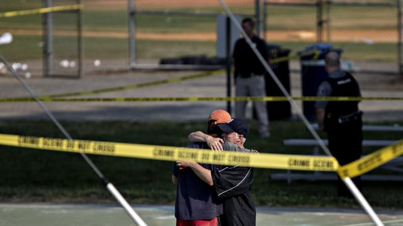Two people embrace near the blocked-off crime scene in Alexandria, Va., where at least five people were wounded in a shooting during a congressional baseball practice Wednesday. The suspected gunman has died, officials say.