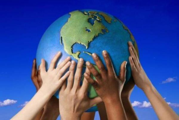 Diverse group of children's ahnds holding up the globe.