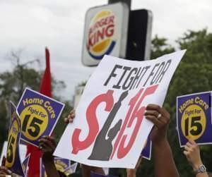 Labor organizers hold banners during a protest to raise the minimum wage for employees to $15 an hour in Illinois.