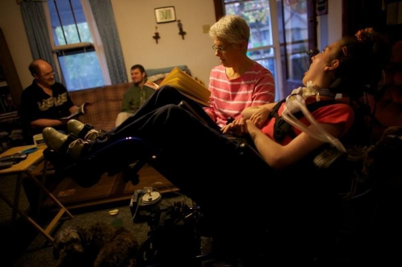Olivia Welter's mom, Tamara, reads to her in the family's living room in 2010, with her father John and brother Brian in Lincoln, Ill. Now, nurses care for Welter 16 hours a day. John and Tamara take over the other eight hours. If they lose