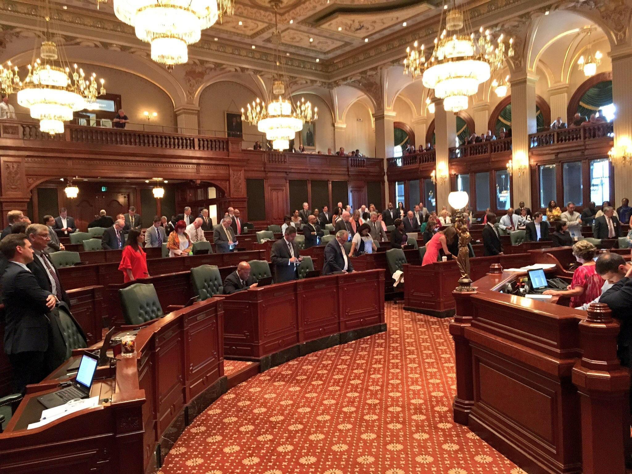 Members of Illinois House of Representatives stand in support of Rep. Jaime Andrade's denunciation of a political cartoon using racial stereotypes to make a point about school funding.