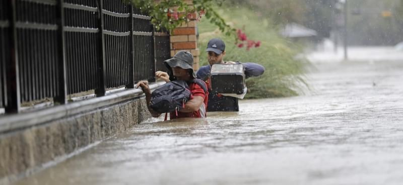 Residents wade through floodwaters from Tropical Storm Harvey on Sunday in Houston, Texas.