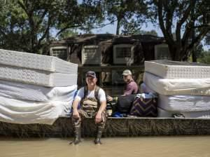 Scott McKnight (left) rides in a boat with his mattresses in the Nottingham Forrest subdivision of Houston on Thursday. Bret Hinkie, a Houston-area commercial airline pilot and a high school friend of McKnight, is volunteering to drive residents to t