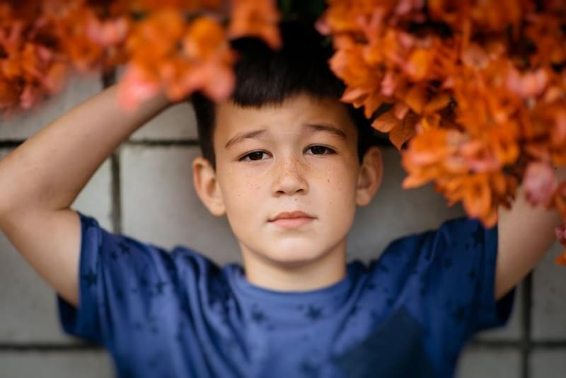 Boy with hands above head in the  orange leaves