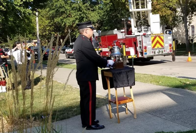Member of Champaign Fire Dept. honor guard rings a bell in memory of those killed in the Sept. 11 2001 attacks.