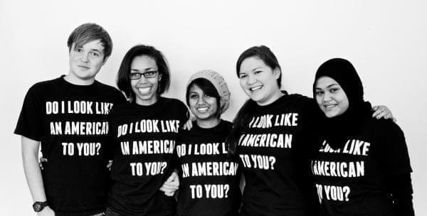 University YMCA students wearing shirts saying 'Do I look American to you?'