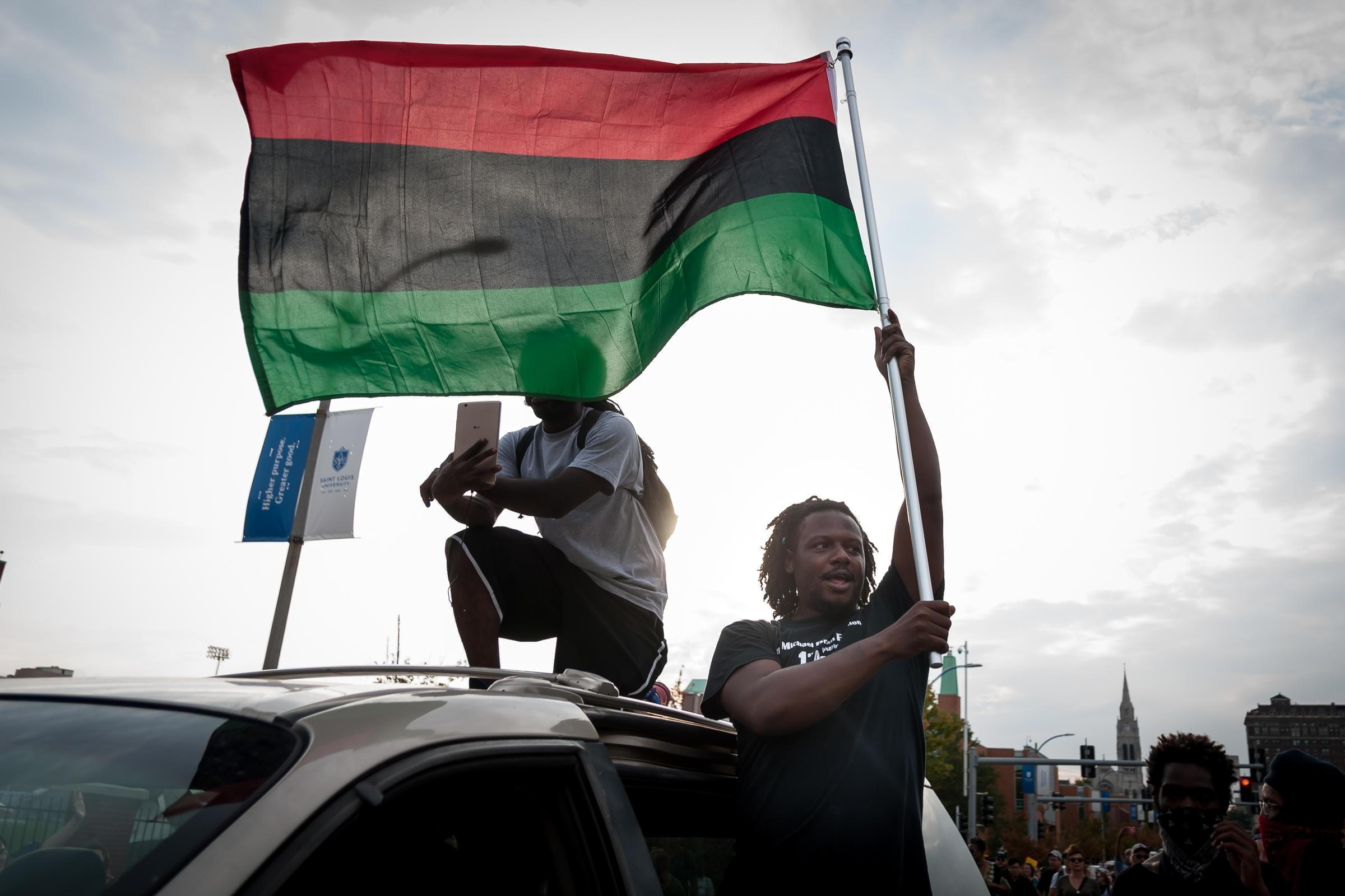 A demonstrator waves a flag from a minivan during protests Sunday over the acquittal of former St. Louis cop Jason Stockey. A third day of protests started peacefully before a smaller group smashed windows downtown.