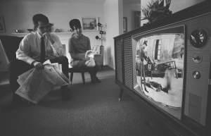 An American man and woman watching footage of the Vietnam War on television in their living room, February 1968