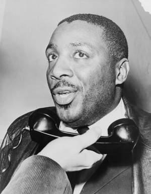 Dick Gregory holding a telephone