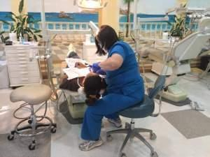 A hygienist numbs a patient in preparation for a tooth extraction at Smiles of Hope.