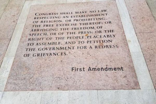 The First Amendment Words written on a sidewalk.