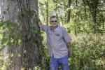 Louis Nelms with a white oak tree that may have been damaged by herbicide drift in rural Atlanta, Ill. on September 30.